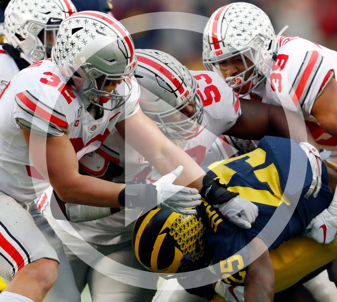 In this file photo, Ohio State linebackers Tuf Borland (32), Davon Hamilton (53) and Malik Harrison (39) smother Michigan running back Hassan Haskins (25) in the second half of an NCAA college football game in Ann Arbor, Mich., in this Saturday, Nov. 30, 2019, file photo. Michigan canceled its annual rivalry game at Ohio State on Tuesday, Dec. 8, 2020, because of the COVID-19 outbreak within the Wolverines football program.