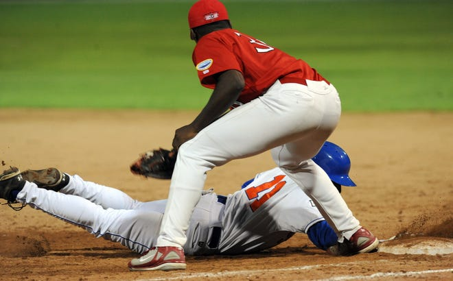 Jackie Bradley Jr., playing for Hyannis, dives safely back to first ahead of the tag by Orleans first baseman Jaren Mathews in June 2009. The Cape League has produced over 1,400 big leaguers.