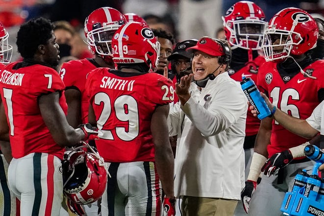 Georgia head football coach Kirby Smart talks to his players during a game against Auburn on Oct. 3 at Sanford Stadium in Athens, Ga.