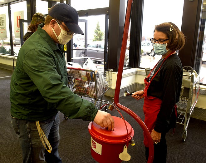 Anthony Smith donates on Friday to the Salvation Army Bell Ringers' Red Kettle as bell ringer Linda Smith rings her bell at the Hy-Vee  at 3100 West Broadway. The Columbia Salvation Army's goal this year is $400,000. So far only 30 percent of the goal has been reached — with less than two weeks until Christmas.