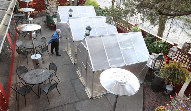 """Barcelona restaurant general manager Tim Hawkins peeks into one of the three """"winter cabanas"""" on the patio of the popular German Village-area restaurant. Hawkins said the structures can handle two seatings per evening and are fully sanitized between groups."""