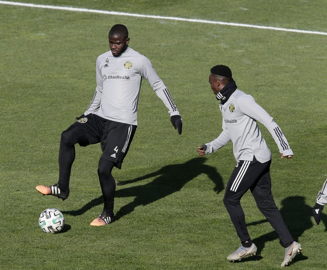 Crew defenders Jonathan Mensah (4) and Harrison Afful run a drill at practice Friday in Mapfre Stadium.