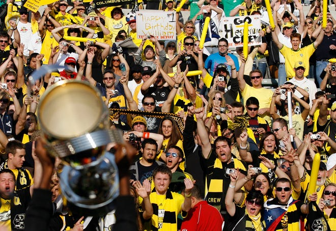 Columbus Crew fans celebrate as a Crew player holds up the MLS Cup trophy after their win over the New York Red Bulls at the Home Depot Center in Carson, California, in 2008.