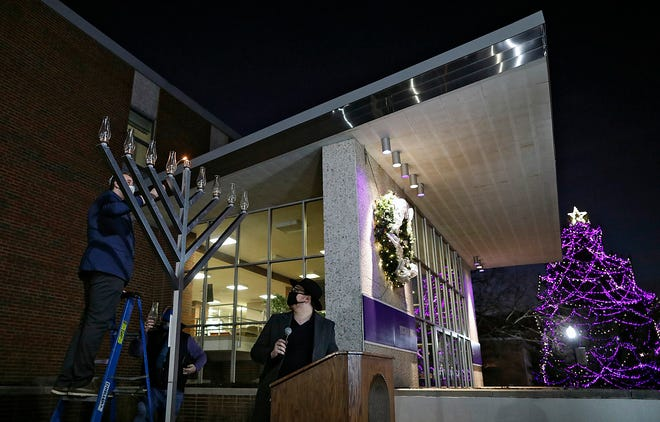 Gareth Evans, a Jewish student representative and senior at Capital University, lights the shammash during a menorah lighting ceremony in front of Yochum Hall at the Bexley university on Dec. 10. The shammash is the candle used to light the others in a Hanukkah menorah.