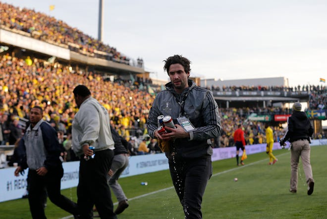 Stadium staff pick beer cans up off the field in the first half of the 2015 MLS Cup final after a controversial no-call near midfield. Those same officials will call the 2020 MLS Cup final.