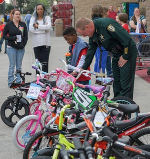 "Lake County Sheriff Peyton Grinnell looks over bikes with a child at the ""Shop with a Cop"" event held at Walmart in Mount Dora on Saturday, Dec. 16, 2017. The Shop-with-a-Cop program was canceled in 2020, leading the agency to donate over $11,000 to Lake Children through the Salvation Army. [PAUL RYAN /CORRESPONDENT]"