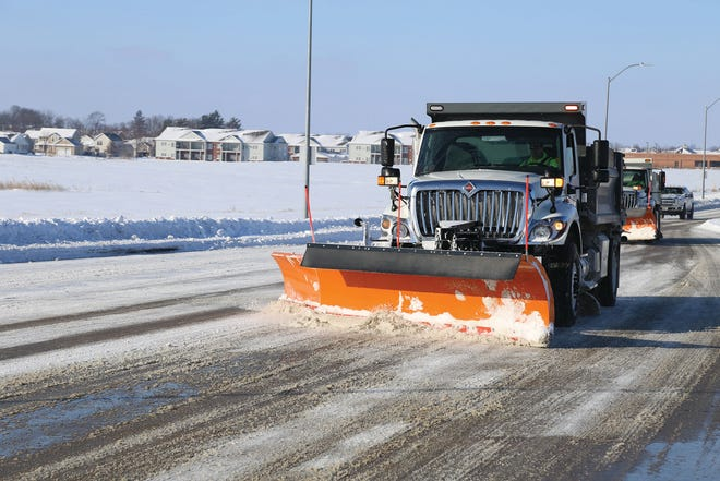 A snow plow goes down a street in Waukee.