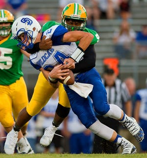 South Davidson quarterback Damon Hill is sacked by West Davidson's Jacobee Dorn in a 2019 game. The Dragons and Wildcats will be conference rivals again starting with the 2021 football season. [Donnie Roberts/The Dispatch]