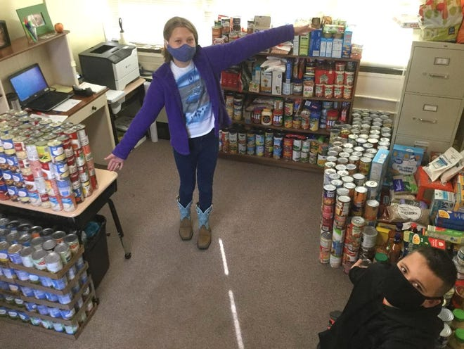 Erika Ledbetter, president of the Student Council at Silver Valley Elementary School, and Seth Snider, vice president (right corner), are surrounded by stacks of food items gathered by students, faculty and staff for Civitan Project Santa.