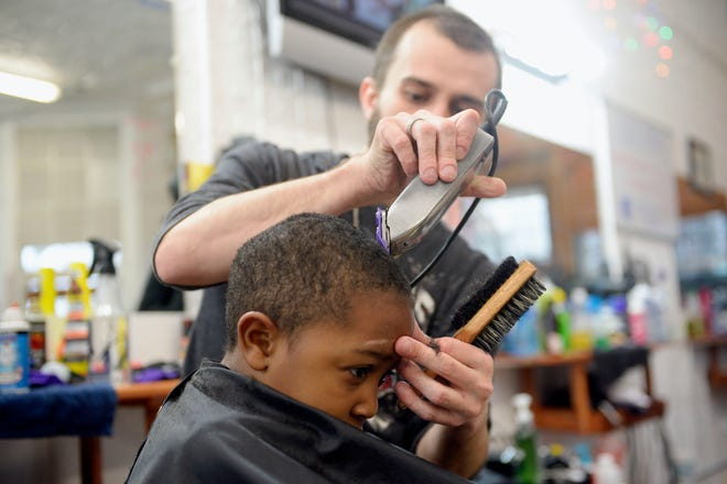 In this file photo, a child receives a haircut at People's Choice Barber Shop in Burlington. People's Choice Barber Shop will provide free haircuts for anyone who needs one from 8 a.m. to 6 p.m. Monday.