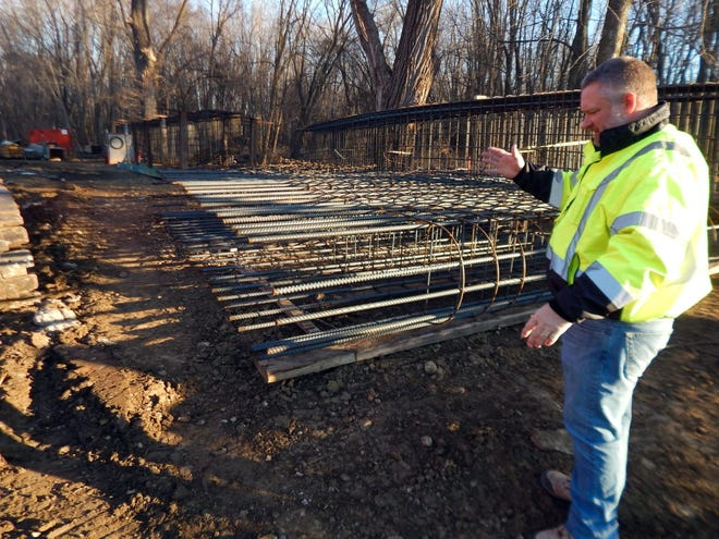 Des Moines County engineer Brian Carter describes the iron forms behind him Wednesday at the site of the DMC 99 bridge in Burlington. The forms will be filled with concrete after installation in Flint Creek and provide the reinforcement in the stem of the two piers that will support the new bridge. The project is expected to keep the road closed until June.