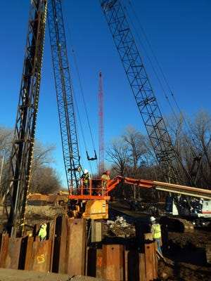 Construction equipment and crew of Iowa Bridge and Culvert install pilings for the new bridge on Highway 99 spanning Flint Creek north of Burlington Dec. 9. In the foreground are some of the 36 50-foot iron H-pilings which will support two T-piers and the roadbed. Two cranes work in tandem: one crane lifts the beam, another lifts the diesel piledriver on the left.