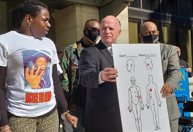 Tawanna Myrick (left), wearing a T-shirt memorializing her 18-year-old son, Devon Tillman Gregory, looks at family attorney Kevin O'Connor (center) as he discusses the independent autopsy and the 13 bullet holes in his body.