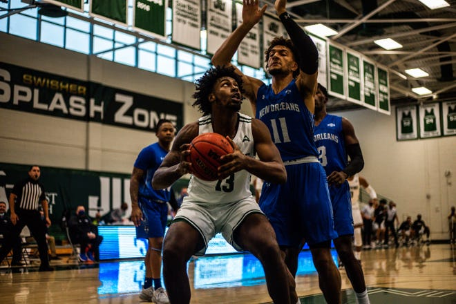 Bryce Workman of Jacksonville University (13) looks for an opening against Ahren Freeman of New Orleans (11) during Thursday's game at Swisher Gym.