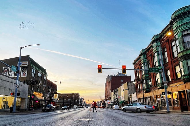 A pedestrian crosses East Main Street at Seminary Street in downtown Galesburg late afternoon on Dec. 10, 2020.