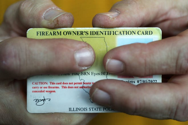 "Mark Jones, a gun safety advocate and retired ATF agent, displays his firearm owner's identification card during an interview in 2019 in Chicago. Jones called a spike in gun purchases in Illinois in 2020 ""a fear-driven surge of purchasing."""