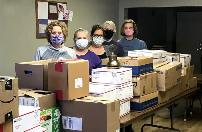 Stephanie Ball, left, Patty Mahon, Nikki Diddens, Sally Brandt, and Shirley Jordan stand behind boxes to be shipped to military personnel on Nov. 23, 2020, in McConnell.
