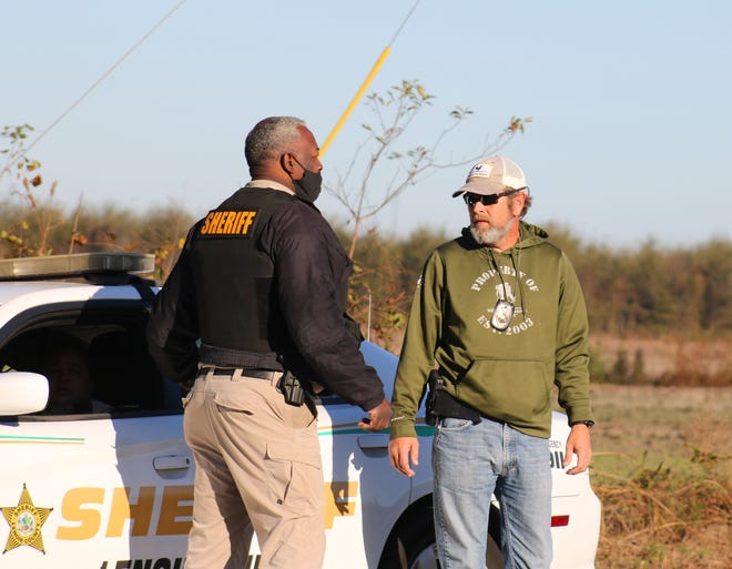 Lenoir County Sheriff Ronnie Ingram talks to a law enforcement agent Friday, Nov. 20, on Kennedy Home Road while officers pursue Robert Lee Strother.