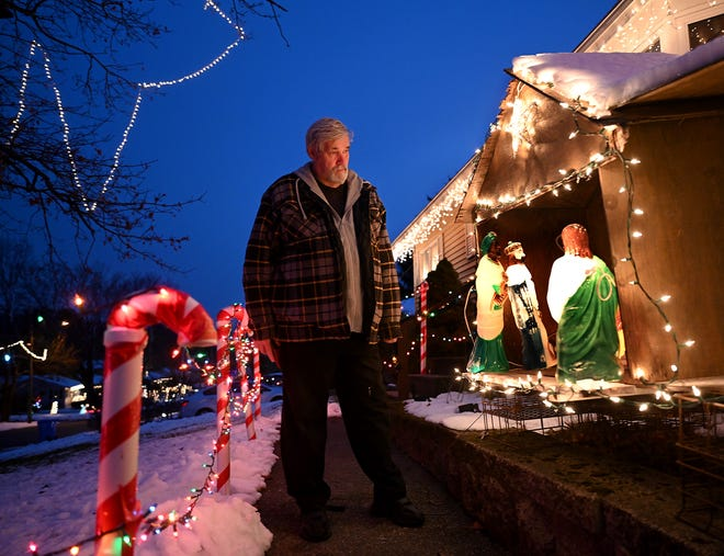 Richard Ball admires his manger in front of his home at 110 Regal St. in Holliston as dusk falls, Wednesday. Ball has created an enormous display for his Regal Street neighborhood, starting with the manger in 1971.