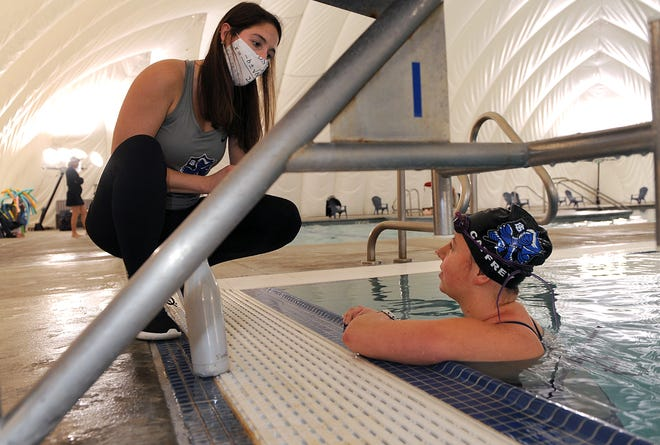 New Dover-Sherborn swim coach and former D-S swimmer,  Carly Eckles (left) with current D-S junior swimmer Jane Caffrey at the Kingsbury Club in Medfield on Dec. 11, 2020.