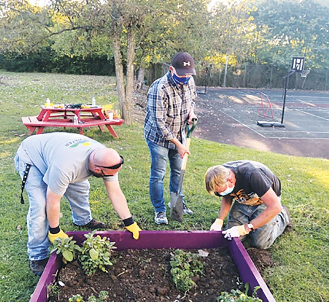 Devrin Kuipers, from left, Kirby Deal and Wes Singer work on a garden bed.