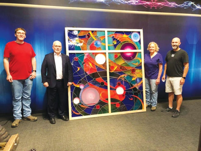 Pictured with the stained glass artwork are Eric Goff, AMSE director Alan Lowe, artist Laura Goff and Oak Ridge City Council member Jim Dodson.