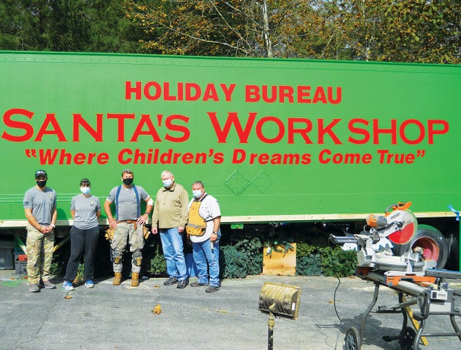 Volunteers from SOS, Saving our Servicemembers, Jamie Uptgraft, from left Sundi Wright, Mike Fierley, Ralph Adcox and Steve Wrzesniewski work on panel doors to be placed beneath the Holiday Bureau trailer behind them. They did their work in October.