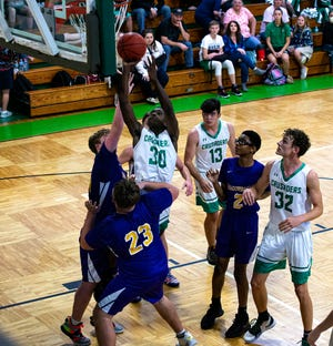 Ocala Christian's Sherrick McGill going up over Meadowbrook defenders Thursday night. The Crusaders defeated the Mustangs, 68-40.