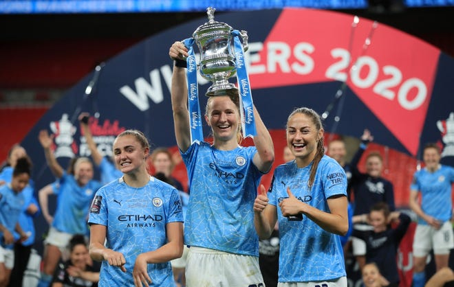 Sam Mewis raises the Women's FA Cup trophy following Manchester City's 3-1 win over Everton at Wembley Stadium in London on Sunday, Nov. 1, 2020. Mewis is flanked by teammates Georgia Stanway, left, and Janine Beckie.