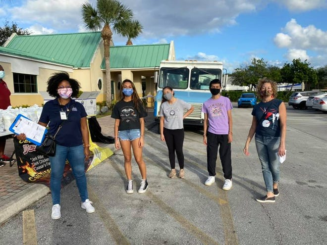 Student volunteers help distribute meals at a drive-thru pick-up event at the Achievement Centers in Delray Beach on Nov. 19.