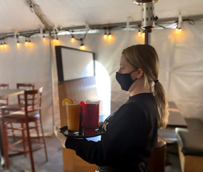 Server Dustie Heller walks beers to a table in a heated outdoor tent at Barley Creek Brewing Company in Tannersville in December, 2020.