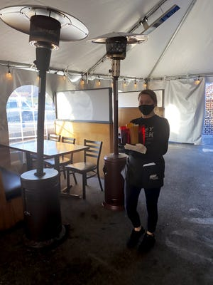 Dustie Heller serves beers in a heated outdoor tent at Barley Creek Brewing Company in Tannersville, Pa. Restaurant owners in the Poconos have questioned state-sanctioned mitigation efforts since the onset of the COVID-19 pandemic.