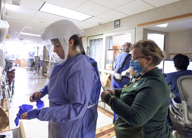 Deb Dalsing, nurse manager of the COVID-19 treatment unit at UW Health in Madison, Wis., assists nurse Ainsley Billesbach with her personal protective equipment.
