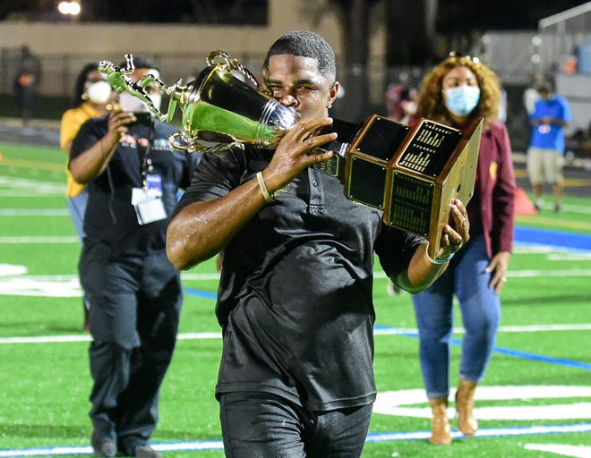 Rashad Jackson, celebrating with the Muck Bowl trophy after Glades Central defeated Pahokee last month, is one of the finalists for Palm Beach County high school football coach of the year.
