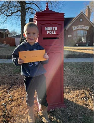 Kyler Christie, 4, son of Jill and Ryan Christie, smiles as he gets ready to mail his Christmas letter to Santa at a special mailbox that has been placed on the square in St. John.