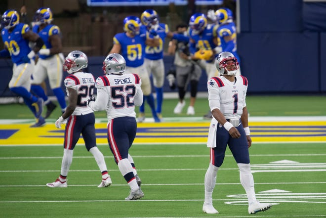 New England Patriots quarterback Cam Newton (right) walks back to the bench after giving up an interception that led to a touchdown by Los Angeles Rams linebacker Kenny Young during an NFL football game on Dec. 10, 2020, in Inglewood, Calif.