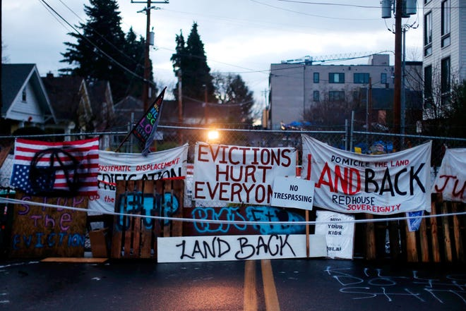 Signs and barricades remain outside a house on North Mississippi Ave. in Portland, Ore., on Wednesday, December 9, 2020. Makeshift barricades erected by protesters are still up in Oregon's largest city a day after Portland police arrested about a dozen people in a clash over gentrification and the eviction of a family from a home. (Beth Nakamura/The Oregonian via AP)