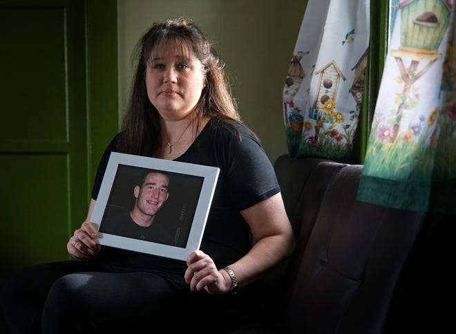 Jennifer Phillips holds a photograph of her son Chad Frank who died from COVID-19. Phillips also caught the virus, but recovered.