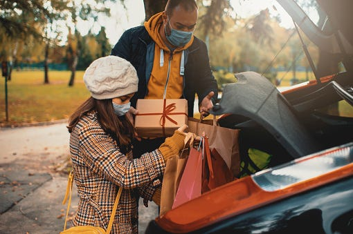 People put gifts in their car after shopping during the coronavirus pandemic. [Getty Images/iStockphoto]