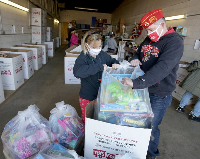 Stark County Toys for Tots personnel Kari Harris (left) and Jeff Weber sort through boxes filled with toys Friday morning at the agency's storage center in northwest Massillon. The annual toy drive is winding down, and delivery will soon begin.