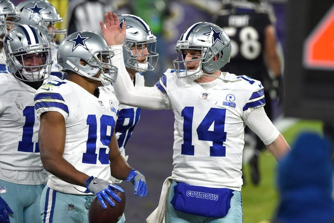 Dallas Cowboys quarterback Andy Dalton (14) and wide receiver Amari Cooper (19) react after they connected for a touchdown pass and catch against the Baltimore Ravens on Tuesday in Baltimore.