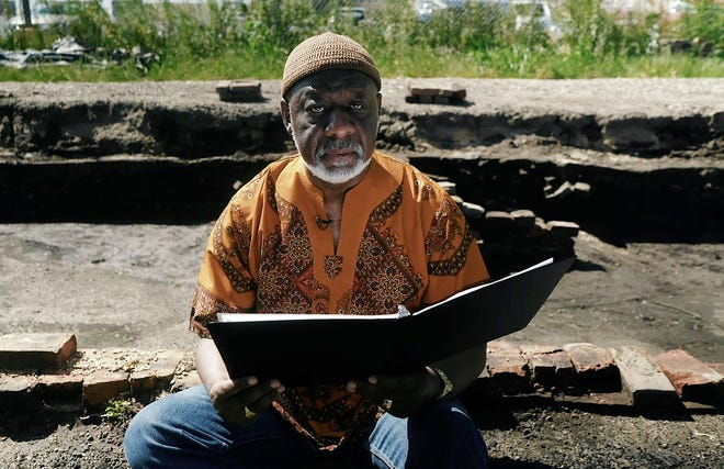 """A still image from the short film """"Face to Face"""" produced by The Storyteller Studios featuring Dr. Wesley Robinson-McNeese performing his poem, """"Face To Face"""" at the archaeological site of a row of houses burned in the Springfield Race Riots of 1908. [Provided by The Storyteller Studios]"""