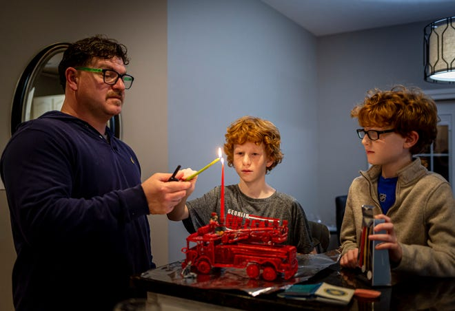 Robert Rabin, a captain with the Springfield Fire Department, helps his twin sons, 10-year-olds Isaac and Ian, light the first candle of a fire engine menorah to mark the first night of Hanukkah on Thursday in Springfield. The fire engine menorah was a gift to Rabin from his mother when he became a firefighter 15 years ago. [Justin L. Fowler/The State Journal-Register]