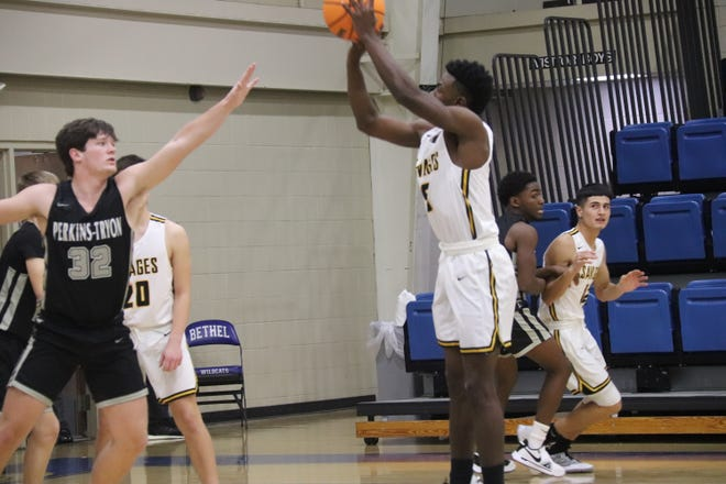 Tecumseh's Daveon Mays (right) puts up a shot over the defense of Perkins-Tryon's Gannon McCutchen Thursday in the First United Bank Classic at Bethel High School's B.E. Cantrell Fieldhouse.