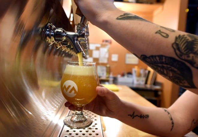 Bartender Carleigh Christy fills up a double IPA at New Anthem Beer Project is located at 116 Dock St. in Wilmington, N.C., Thursday, February 28, 2019. [Matt Born/StarNews Photo]