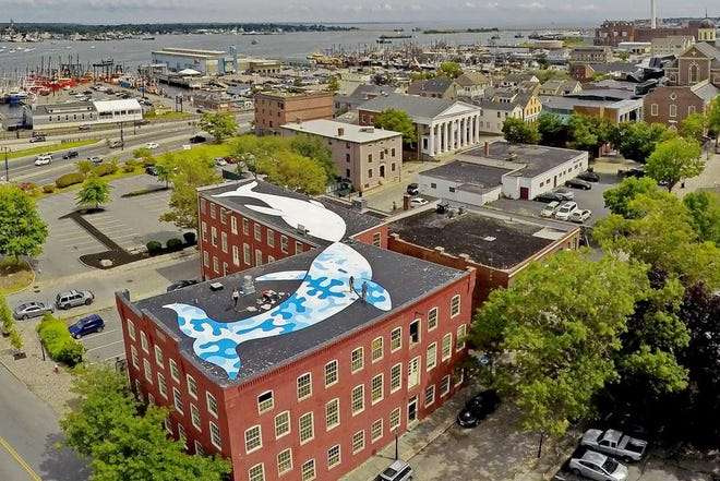 FILE PHOTO: Acclaimed New York City artist Tom Bob returned to his native New Bedford to paint two whales on the roof of a building complex on Elm Street at the edge of the New Bedford Historical Whaling Park.