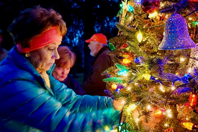 Jean Bender aids in decorating the Christmas tree on Main Street in Pollocksville. [CONTRIBUTED PHOTO]