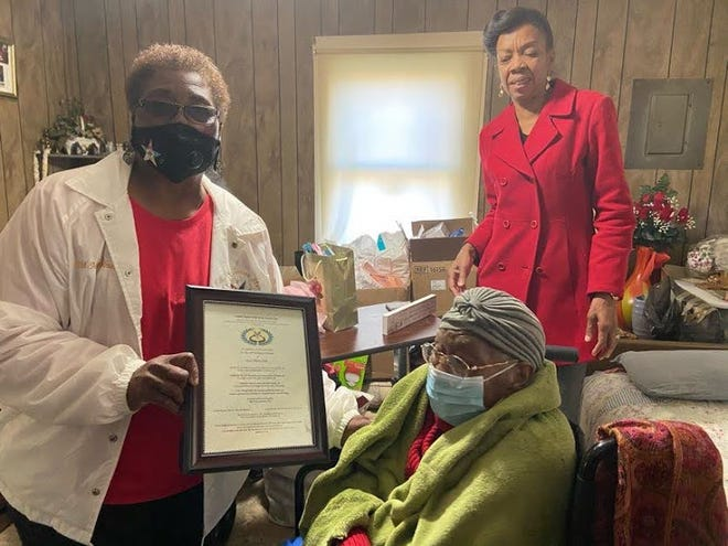 Members of Joy Chapter Order of the Eastern Star, Worthy Matrion Sis. Martina Midgett and Secretary Pamela Woods, along with Deputy of District 6 Sis. Mary S. Holmes, showered its oldest member of the chapter, Sis. Alberta Jones with gifts and love. Sister Jones recently celebrated her 100th Birthday.  Deputy Holmes presented her with a Proclamation from the Grand Worthy Matron, Sis. Mary McGhee, Grand Worthy Patron Bro. Reginald McClenton and the Most Worshipful Grand Master The Honorable Daniel L. Thompson. Along with this the district showered her with cards and joined in with her church with a parade of love. While visiting, Sister Jones she sung her favorite song Draw Me Nearer. Pictured, District Deputy Mary Holmes presents proclamation to Ms. Alberta Jones, while her granddaughter looks on. [CONTRIBUTED PHOTO]