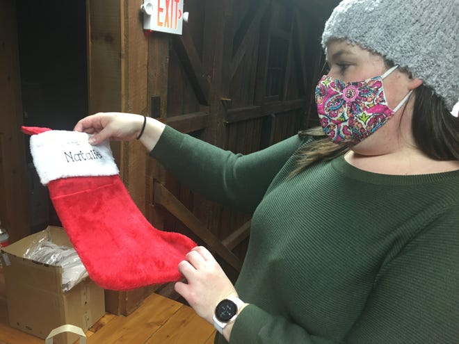 Rose City BNI secretary Dana Dowdell looks at a stocking with the name of a youth receiving from the toy drive this year.