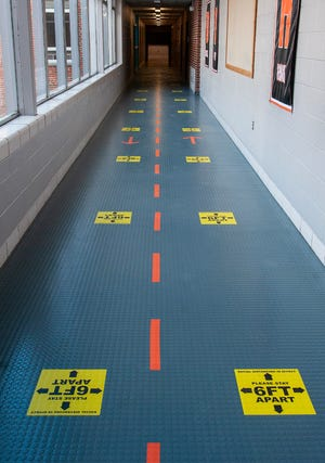 A hallway is marked for social distancing at David Prouty High School in Spencer.